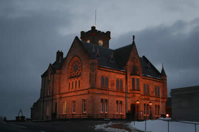 Midnight oil is being burned at Lerwick Town Hall aa councillors ands officials work out how to make extra savings after this week's shock of a 4.5 per cent cut to their government grant.